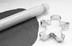 Gingerbread dough, rolling pin and cookie cutter - stock photo