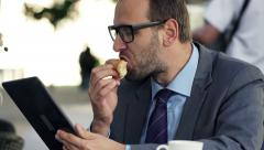 Young businessman with tablet computer eating croissant in cafe in city  HD Stock Footage