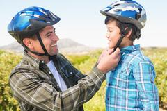 Father attaching his son cycling helmet - stock photo