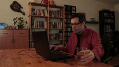 Man with glasses typing on laptop computer and takes glass of water and drink. Stock Footage