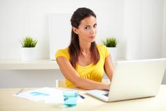 Adult female in yellow clothes working as a receptionist in a company Stock Photos