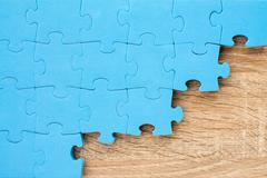Jigsaw puzzle on wooden background - stock photo