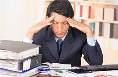 Stock Photo of young stressed overwhelmed man with piles of folders on his desk