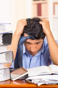 Young stressed overwhelmed man with piles of folders on his desk Stock Photos