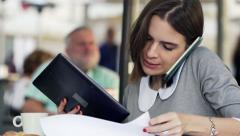 Busy, multitasking businesswoman sitting in cafe in city HD Stock Footage