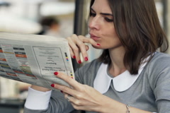 Young businesswoman reading newspaper sitting in cafe in city NTSC Stock Footage