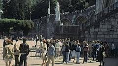 Lourdes 1978: people walking under Virgin Mary statue Stock Footage