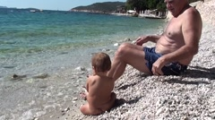 Own baby and adult on the beach Stock Footage