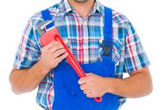 Cropped image of repairman holding monkey wrench Stock Photos
