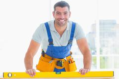 Smiling handyman using spirit level in office Stock Photos