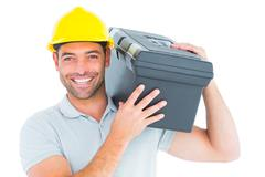 Confident handyman carrying toolbox on shoulder Stock Photos