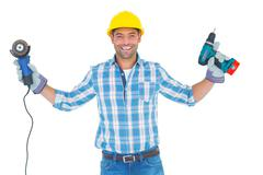 Manual worker holding power tools - stock photo