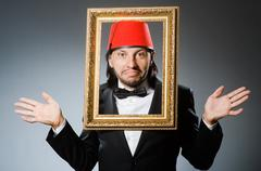 Man with fez  hat and picture frame Stock Photos