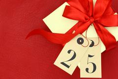 Gift box with and tags with number 25 on red background - stock photo