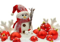 Snowman and Christmas ornaments on snow - stock photo