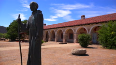 A statue of Father Junipero Serra stands in front of a California Mission. - stock footage