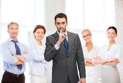 Stock Photo of group of smiling businessmen making hush sign