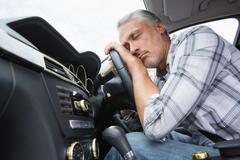 Drunk man slumped on steering wheel Stock Photos