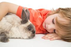 Cute boy lying arm around bunny Stock Photos