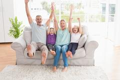 Family of four with arms raised sitting on sofa Stock Photos