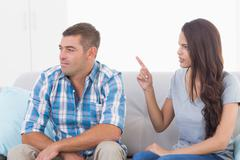 Woman arguing with man while sitting on sofa Stock Photos