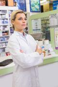 Junior pharmacist with arms crossed - stock photo
