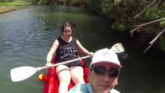 Couple riding canoe in river Stock Footage