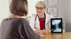 Senior doctor tablet talking x-ray - stock footage