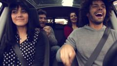 Four happy cool people having fun in car - stock footage