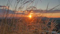 4K Crane Shot Through Grasses and Setting Sun on Distant Hills, Blue Orange Sky Stock Footage