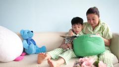 Happy asian family reading a book together on sofa at home Stock Footage