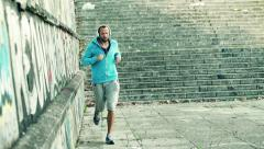 Stock Video Footage of Young man with headphones jogging by graffiti wall in city, slow motion HD