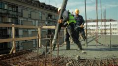 Two workers pulling big hose for concreting slab of steel reinforced concrete. Stock Footage