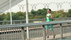 Young woman jogging on bridge in the city HD Stock Footage