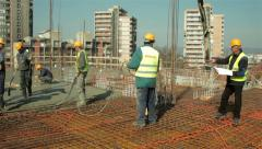 Construction manager supervise workers at construction site. Concreting building - stock footage