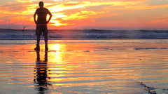 A man stands silhouetted in golden sunset light along the Central California Stock Footage