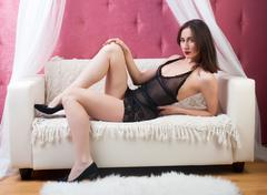 Young woman in black lingerie on sofa Stock Photos