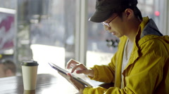 Multi-Ethnic Man Uses His Tablet At A Coffee Shop Stock Footage