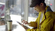 Stock Video Footage of Multi-Ethnic Man Uses His Tablet At A Coffee Shop