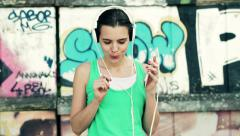 Happy woman listening to music on cellphone standing by graffiti wall in city HD - stock footage