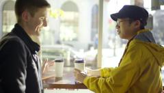 Multi-Ethnic Man Uses His Smartphone, His Boyfriend Arrives With Coffee Stock Footage