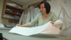 Seamstress puts markings on fabric. Tailoring, аpparel manufacturing - stock footage