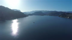 Flying over lake Bled with small boat on sunny day 4K Stock Footage