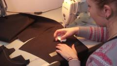 The seamstress works with a piece of black fabric. Tailoring - stock footage