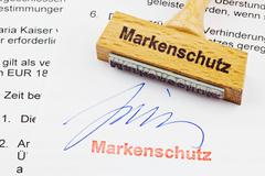 Wood stamp on the document: brand protection Stock Photos