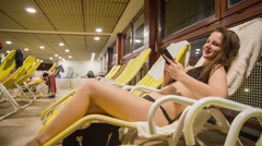 Person at indoor pool on deckchair typing on smartphone Stock Footage