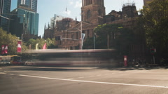 A 4k tilt down as clouds roll over people and traffic at Sydney Town Hall Stock Footage