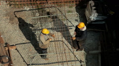 Workers together tied rebar with wire at construction site. View from building. Stock Footage
