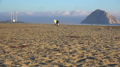 A surfer crosses in front of the beautiful Morro Bay rock along California's Stock Footage