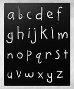 Complete english alphabet handwritten with white chalk on a blac Stock Photos